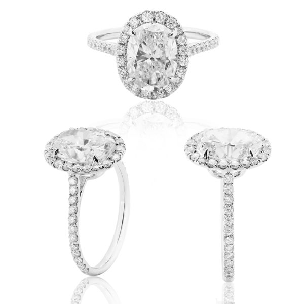 Platinum and Diamond Engagement Ring with centre oval Diamond and Saw set small Diamonds in a Halo setting